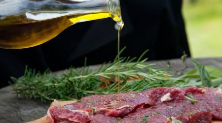 Cooking ingredients: marinated meat,oil,vinegar, herbs and vegetables